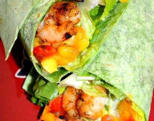 A tortilla with crisp romaine lettuce, bbq seasoned shrimp, mango salsa wrapped up