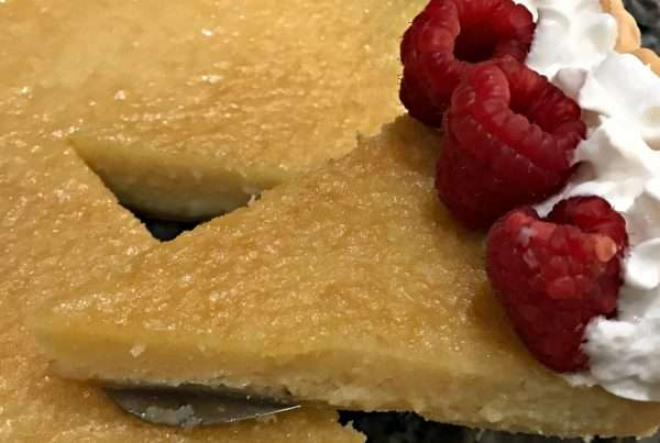 Custard pie made with grits in pie crust served with whipped cream and berries